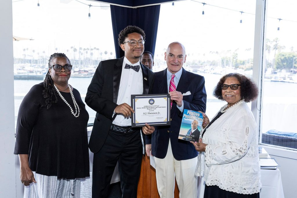 AJ Smith receiving his certificate, book, and scholarship.